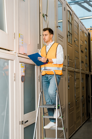 handsome, serious warehouse worker with clipboard standing on ladder in doors department