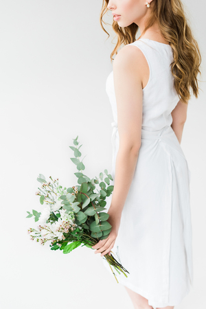cropped view of woman in elegant dress holding flowers isolated on white Reklamní fotografie