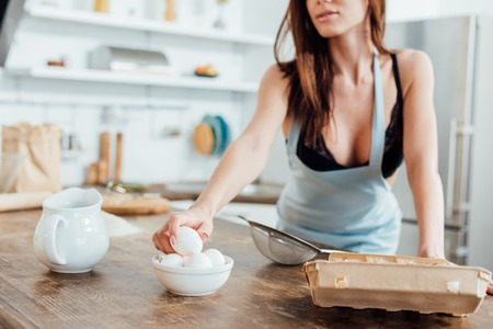 Cropped view of woman in underwear and blue apron holding eggs in kitchen