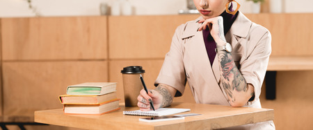 partial view of cafe owner sitting at table in cafe and writing in notebook