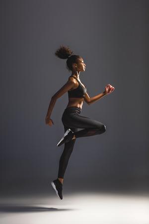 side view of beautiful athletic african american sportswoman jumping on black Reklamní fotografie