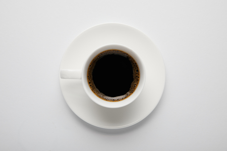 Top view of cup of black coffee and saucer on white