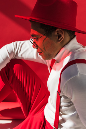 side view of fashionable mixed race man in hat and suspenders posing on red