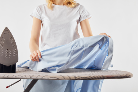 Cropped view of girl ironing blue shirt isolated on white 写真素材