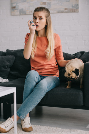 beautiful blonde woman allergic to dog using inhaler while sitting near cute dog at home Foto de archivo