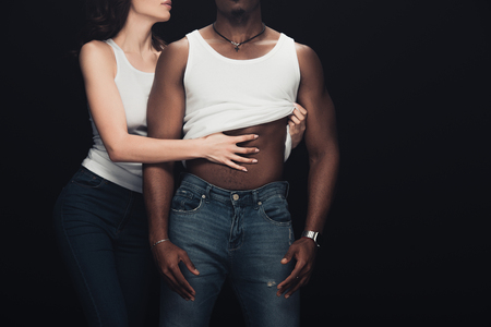 cropped view of woman undressing muscular african american man isolated on black with copy space
