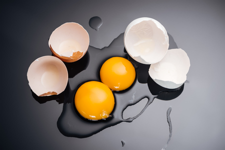 top view of raw smashed chicken eggs with yolks, proteins and eggshell on black background