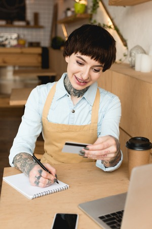 smiling waitress looking at credit card and writing in notebook