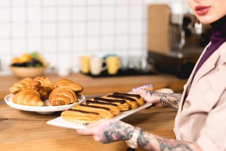 cropped view of cafe owner placing dish with eclairs on bar counter in coffee shop Stock Photo