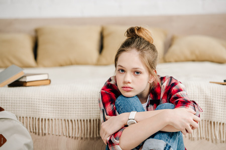 Bored teenager in checkered shirt sitting near bed and embracing knees Stockfoto