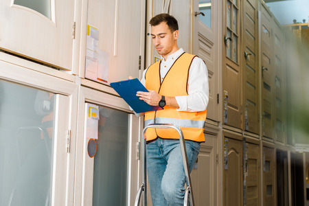 selective focus of concentrated worker with clipboard standing on ladder in warehouse