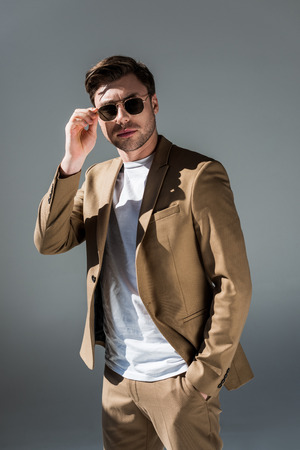 handsome trendy man in beige suite and sunglasses looking at camera on grey