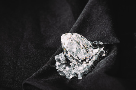 sparkling big diamond among small on black textured shiny cloth