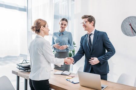 cheerful recruiter shaking hands with woman near colleague in office Foto de archivo - 121416354