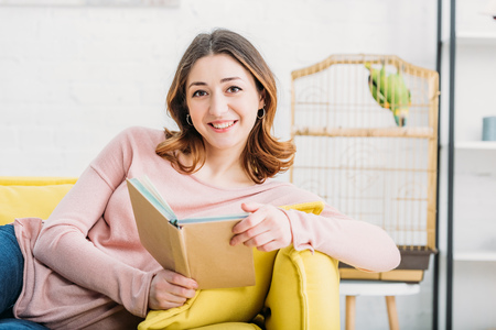Attractive woman holding book and looking at camera at home Banque d'images - 120879304