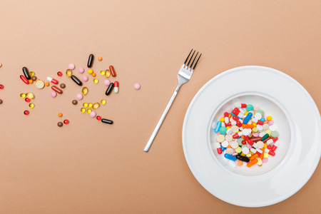 Top view of bowl with pills and fork on brown surface Banco de Imagens