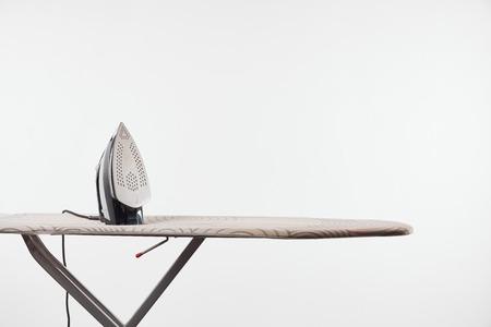 Tabla de planchar con patas oscuras y plancha aislado sobre fondo blanco.