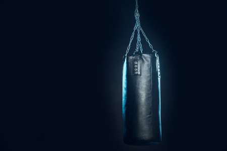 Leather punching bag hanging on steel chains on black Stockfoto
