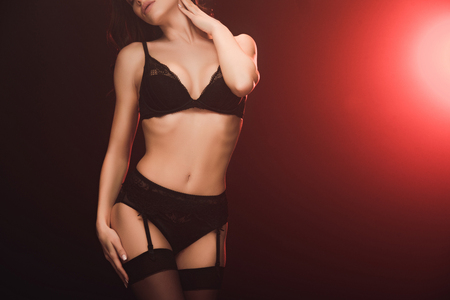 Cropped view of sexy woman in lace lingerie and stockings posing on black with red light and copy space Stock Photo