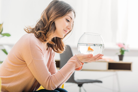 beautiful smiling woman holding aquarium with gold fish at home Stock Photo