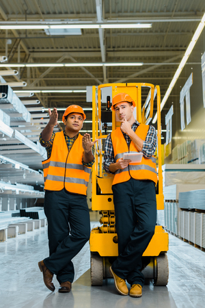 Handsome Indian worker pointing with hands while standing with colleague near scissor lift 免版税图像