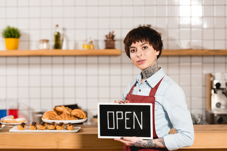 attractive barista holding signboard with open lettering and looking at camera
