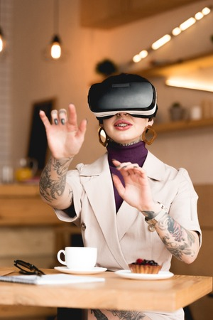 smiling businesswoman in virtual reality headset sitting at table in cafeteria Foto de archivo