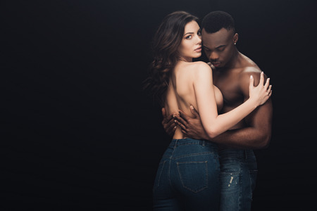 beautiful seductive half-naked interracial couple embracing isolated on black with copy space