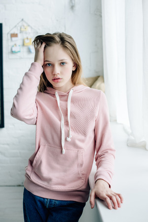 Teenage kid in pink hoodie standing near window sill and touching hair