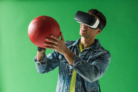 Mixed race man in virtual reality headset holding basketball and smiling on green screen background Stock Photo