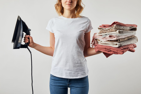 Partial woman in t-shirt holding iron and folded ironed clothes isolated on grey background
