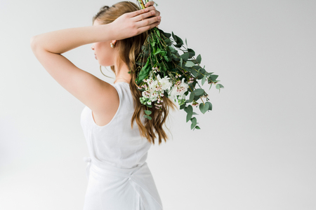 A girl in dress holding flowers behind back on white background
