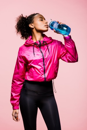 Beautiful African American sportswoman drinking water from sport bottle isolated on pink background