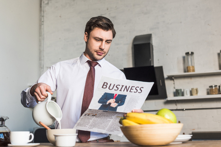 Handsome man reading business newspaper while standing by kitchen table and pouring milk into bowl Banque d'images - 120879394