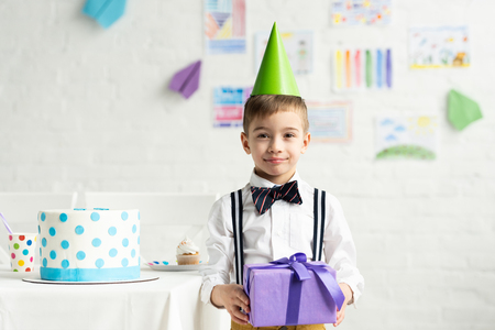 Adorable boy in party cap looking at camera and holding present during birthday celebration