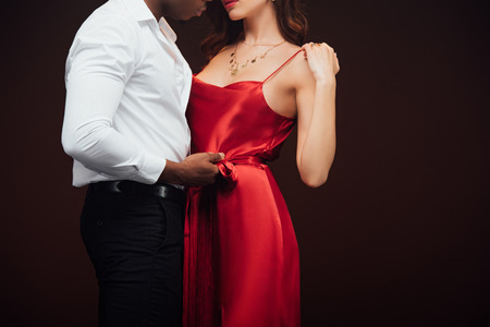 Cropped view of African American man embracing woman in red dress isolated on black with copy space