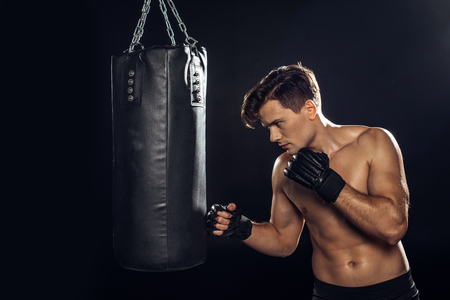 Handsome boxer in boxing gloves training with punching bag on black background