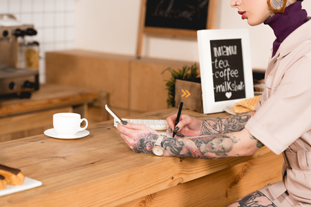 Partial view of businesswoman holding smartphone and writing in notebook while sitting at bar counter Banque d'images - 120879110