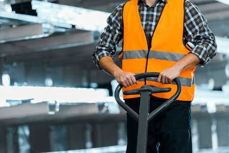Partial view of warehouse worker in safety vast standing with pallet jack 写真素材