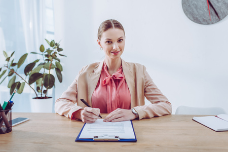 Cheerful and attractive recruiter holding pen near clipboard in office