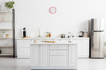 Modern white kitchen with table and kitchenware and fridge Banco de Imagens