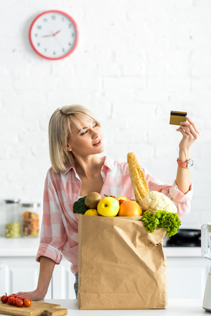 Attractive girl holding credit card near paper bag with groceries