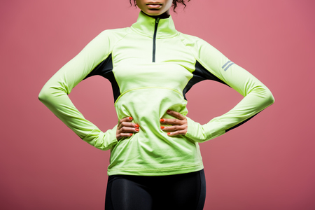 Cropped view of African American sportswoman in track jacket posing with hands akimbo isolated on pink background