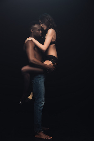 african american man holding in arms beautiful woman in lingerie isolated on black with copy space