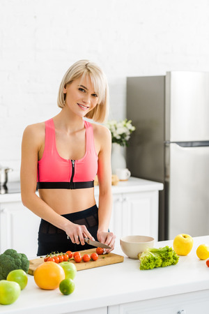 cheerful blonde woman in sportswear cutting cherry tomatoes in kitchen