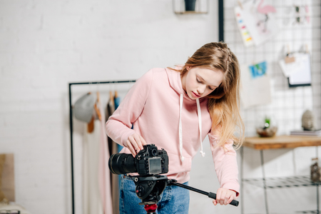 Teenage blogger in pink hoodie setting up video camera at home