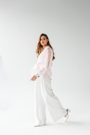 attractive and stylish young woman walking on white