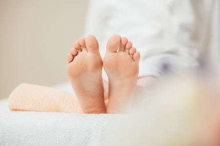 Selective focus of adult woman lying on beige towel in spa