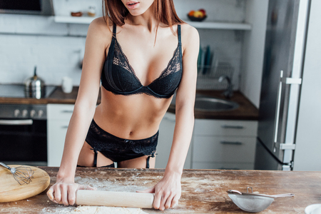Cropped view of sexy woman in black lingerie rolling out dough with rolling pin Фото со стока