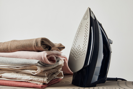 Iron and folded ironed clothes on ironing board isolated on grey background 写真素材